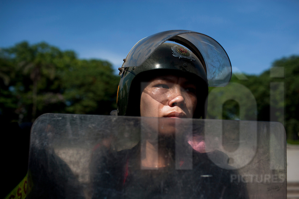 A portrait of a riot police officer monitoring a protest against China's invasion of Vietnam's lands, Hanoi, Vietnam, Southeast Asia