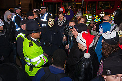 "London, December 23rd 2014. Online activism group Anonymous march through London from the City to the BBC's HQ on Great Portland Street in protest against alleged biases and coverups of a ""paedophile ring"". PICTURED: Protesters discuss their position with a City of London police officer."