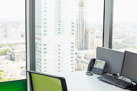 Desktop computer and landline phone on desk by glass window in office