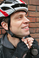 Bicyclist adjusting his helmet