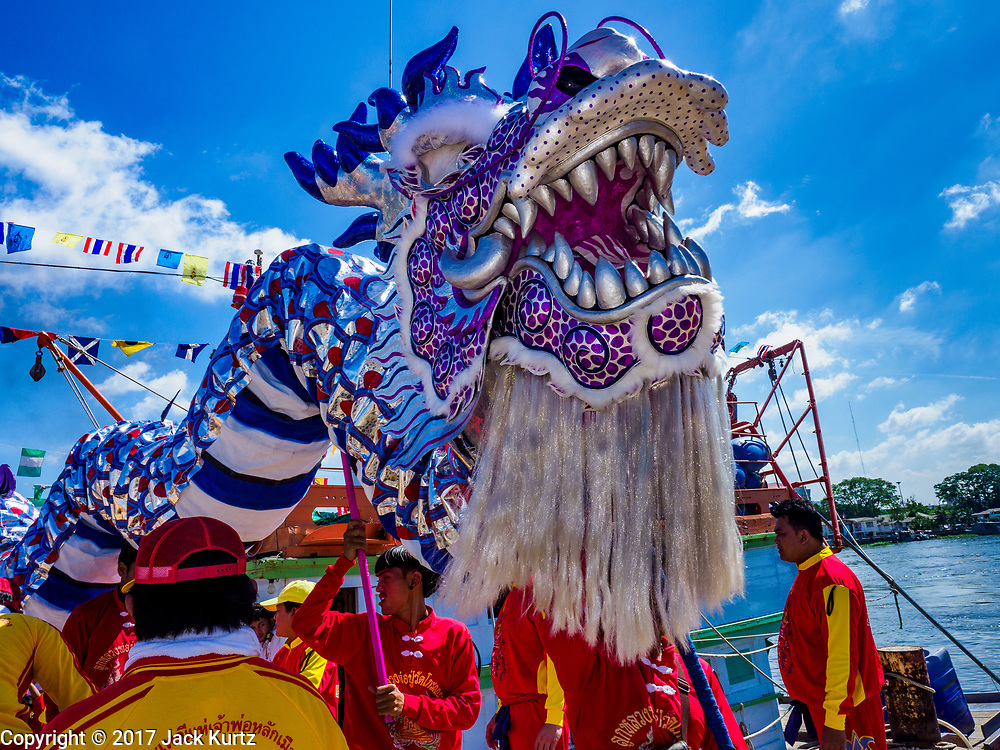 """02 JUNE 2017 - SAMUT SAKHON, THAILAND: Dragon dancers get off a boat that carried them up the Tha Chin River during the procession for the City Pillar Shrine. The Chaopho Lak Mueang Procession (City Pillar Shrine Procession) is a religious festival that takes place in June in front of city hall in Samut Sakhon. The """"Chaopho Lak Mueang"""" is  placed on a fishing boat and taken across the Tha Chin River from Talat Maha Chai to Tha Chalom in the area of Wat Suwannaram and then paraded through the community before returning to the temple in Samut Sakhon. Samut Sakhon is always known by its historic name of Mahachai.      PHOTO BY JACK KURTZ"""