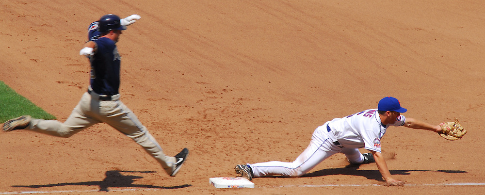 NY Mets vs San Diego Padres; A low throw in the dirt and off the bag dug out by rookie first baseman Evans completes a spectacular double play to end the inning.