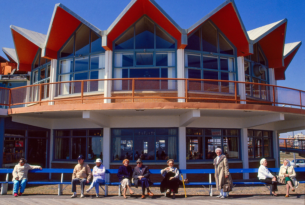 Senior citizens sitting on the Asbury Park boardwalk in early spring in front of the Howard Johnsons