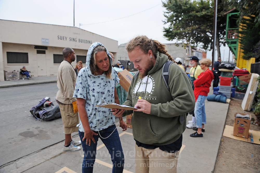 Carol Hernandez checks in CSUMB's Tyler Gidney regarding her temporary storage during Thursday's sweep of Chinatown homeless encampments by the city of Salinas. The 4' by 4' box on the sidewalk outlines how much each resident can store.