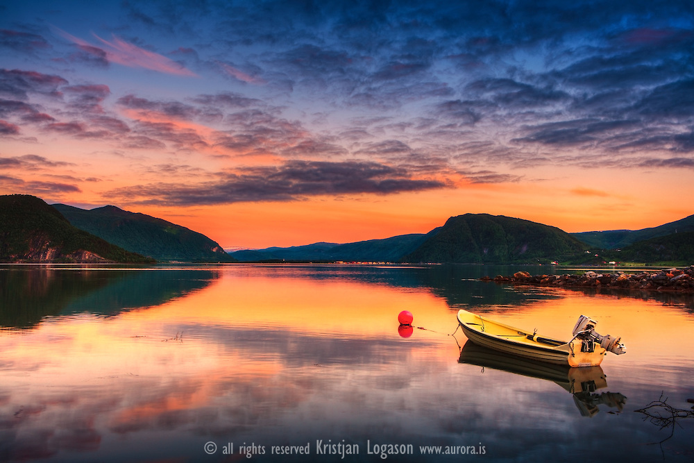 Reflectiv sunset and a yellow boat on a calm evening in Rognan North Norway