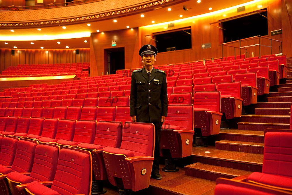 The palace of the Grand  Theater, cinemas and auditorium. These days were held rehearsals for the opera Time to say goodbye. A guard stands in the Grand Theatre,<br /> *** General Caption ***<br /> China became an urban society in 2011, when for the first time the number of city dwellers exceeded the rural population, indeed, the 51% of the Chinese population live in cities, as in 1979, at Deng Xiaoping's time, it was 19%. A report from the McKinsey Global Institute projected that between 2009 and 2025, 350 million people would move from China&rsquo;s rural parts to its eastern cities. <br /> The migrations are expected and driven towards the city of second and third size. These new cities, which are often zoned as new districts of existing municipalities, are built up from scratch, topped off with public works infrastructure, schools, government buildings, stores, malls, massive amounts of housing, universities, and sometimes even stadiums all before a single resident moves in.<br /> The benefits of this urban development strategy are that an entire city can be built on a single, fully integrated plan, but the risks are absolute: if the project fails, an entire city goes under. Nowadays the Kangbashi district, built on the north bank of the Wulan Mulun River, planned to accommodate a population over of one million, is home to a lonely 10,000 people &ndash; leaving more than 98% of this 355-square kilometer site either under construction or abandoned altogether. Housing prices have fallen from $1,100 to $470 per square foot, over the last five years.