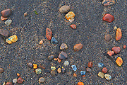 Pebbles on sandy beach at sunrise<br />