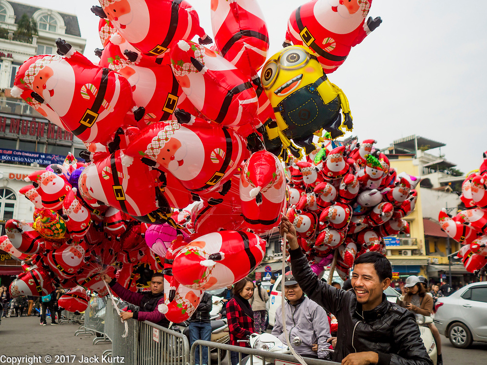 24 DECEMBER 2017 - HANOI, VIETNAM: Inflatable Santa Claus toy venders at a holiday street fair in the old quarter of Hanoi. The commercial and gift giving aspect of Christmas is widely celebrated in Vietnam and Vietnam's 5+ million Catholics celebrate the religious aspects of Christmas.     PHOTO BY JACK KURTZ