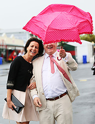 Louise Colleally and her husband Albert, from Athenry, struggle with their umbrella ahead of the start of racing on day three of the Galway Summer Festival at Galway Racecourse.