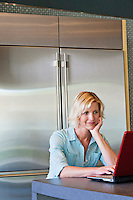 Senior woman with hand on chin using laptop