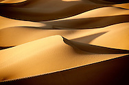 Picture of sand dunes in the Sahara desert of Morocco with strong shadows.