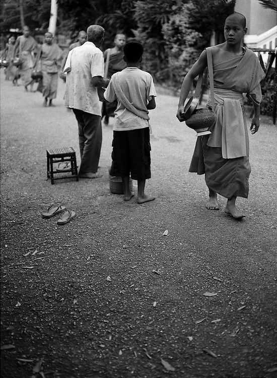 Morning procession of monks receive offerings of food by local residents.
