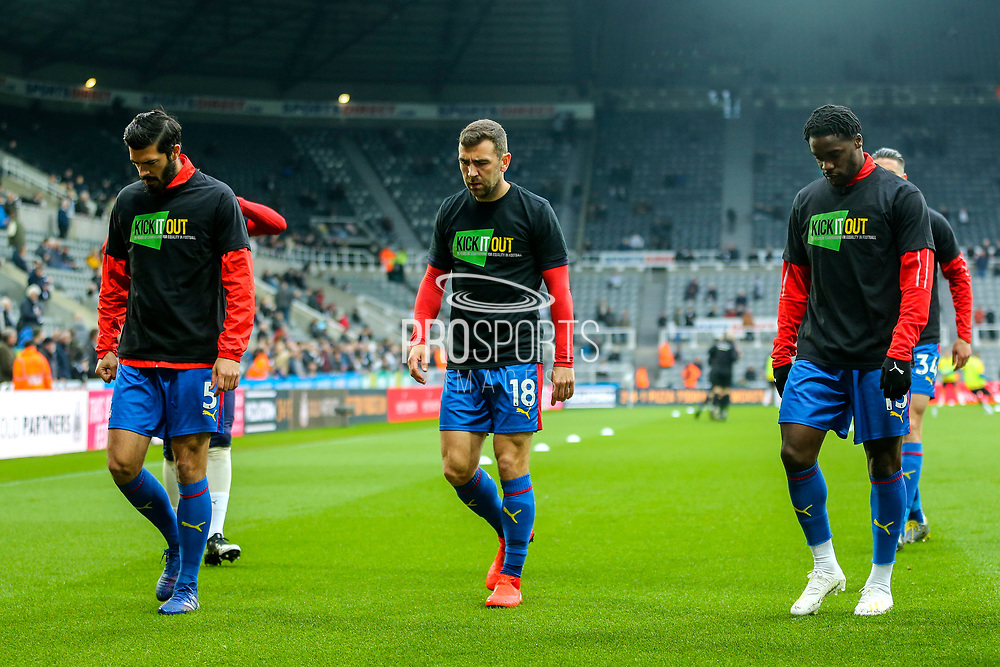 James Tomkins (#5) of Crystal Palace, James McArthur (#18) of Crystal Palace and Jeffrey Schlupp (#15) of Crystal Palace wear 'Kick It Out' campaign t-shrts as part of the warm-up ahead of the Premier League match between Newcastle United and Crystal Palace at St. James's Park, Newcastle, England on 6 April 2019.