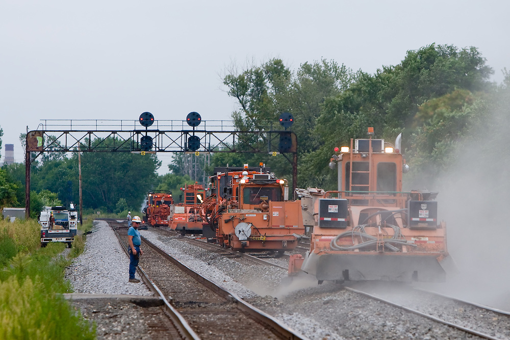 An army of track maintenance machinery go to work on the Norfolk Southern mainline through Whiting, IN, stirring up dust.