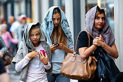 © Licensed to London News Pictures. 13/08/2015. London, UK. People shelter themselves during heavy rain in Knightsbridge, London on Thursday, August 13, 2015. Photo credit: Tolga Akmen/LNP