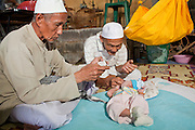 "Sept. 28, 2009 -- TANJONG DATO, THAILAND: The village Imam leads a Tahnik ceremony for newborn baby Nikbukharin while the baby's grandfather holds him in the Muslim village of Tanjong Dato, in the province of Pattani, Thailand. The Tahnik ceremony is a naming ceremony, performed when the baby is one week old. Everybody in the village is Muslim and they say they have no problems, but the roads around the village leading to the provincial capital of Pattani are too dangerous for them to use once it gets dark. Thailand's three southern most provinces; Yala, Pattani and Narathiwat are often called ""restive"" and a decades long Muslim insurgency has gained traction recently. Nearly 4,000 people have been killed since 2004. The three southern provinces are under emergency control and there are more than 60,000 Thai military, police and paramilitary militia forces trying to keep the peace battling insurgents who favor car bombs and assassination.   Photo by Jack Kurtz / ZUMA Press"
