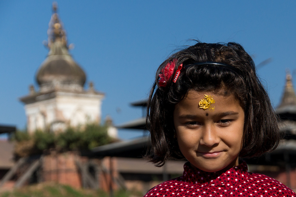 This image is of a Nepali girl who had just received her blessing from the pandit along the Bagmati River.  She had just walked away from her dad who was receiving a blessing as well.  The yellow rice on her forehead is a symbol of longevity and eternal happiness.