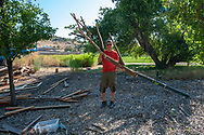 Gregg Mizuta shows the branch he helped construct with his daughter Megan Mizuta. It includes a branch from a tree she planted several years ago. The constructed branch will be incorporated into MING Studios artist-in-residence Han Seok Hyun large scale, permanent sculpture, entitled Reverse-Rebirth at Idaho Botanical Garden on July 21, 2018 in Boise, Idaho.<br /> <br /> Han Seok Hyun connected with the Boise community through gathering furniture and cast off wood pieces, seeds and plants, which will be used to build up his sculpture.<br /> <br /> The work of Korean artist Han Seok Hyun addresses the dichotomy of ''artificial nature,'' calling attention to man&rsquo;s handling of the natural world observable in contemporary urban environments. In Reverse-Rebirth, Han takes nature into his own hands. Reclaimed wood, discarded furniture, native plants, and locally foraged seeds compose the monumental tree-like sculpture that continuously evolves over time and throughout the seasons. The work reaches for a symbiosis with the given environment, while Han pushes the boundaries of a domesticated relationship with Mother Nature.