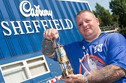 Cadbury 2012 Paralympic demonstration Sheffield..Steve Gill former soldier and Big Brother Contestant in 2010 and now coach and player with the Leicester Cobras Wheelchair Basketball team pictured with the paralympic torch outside Kraft Foods (formerly Basset's factory) Sheffield...3 September 2012.Image © Paul David Drabble
