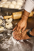 An Indian chef prepares naan bread.