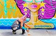 Artist Claudia LaBianca spray-painting a  mural at a vintage thrift store in Miami's  high trending Wynwood neighborhood