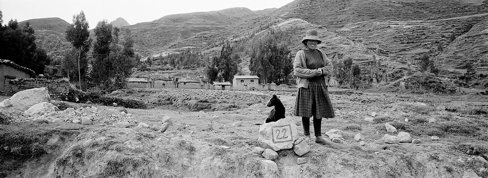 Woman and dog sitting on 22 sign rock, Peru