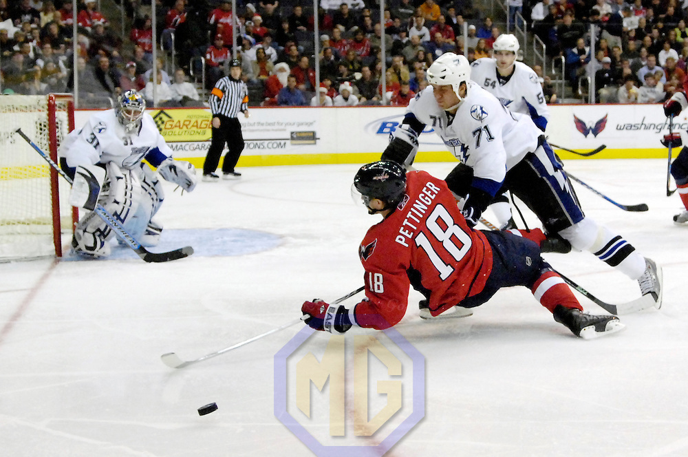 26 December 2007:  Washington Capitals left wing Matt Pettinger (18) is knocked down to the ice in the second period by Tampa Bay Lightning defenseman Filip Kuba (71) as the puck bounds away at the Verizon Center in Washington, D.C.  The Capitals defeated the Lightning 3-2.
