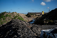 A migrants is seen walking between hills of industrial waste. Here hundres migrants and refugee are living waiting to cross the channel to UK. Calais. France. FEDERICO SCOPPA