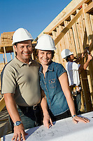 Couple in hard hats with blueprint on house construction site portrait