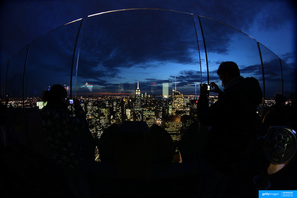 A panoramic fisheye view of Manhattan, New York, at night time as tourists take pictures of  New York from the Top of the Rock, the observatory deck at Rockefeller Center showing the Empire State Building, Manhattan, New York, USA.  Photo Tim Clayton