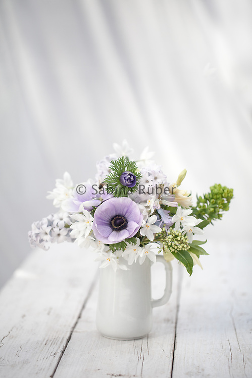 Spring arrangement with pale blue Anemonies coronaria, Narcissi, Hellebore Euphorbia and Hyacinths