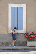 Woman looking shocked at cell phone, village of Villars, Provence,France<br /> MR 0350