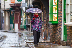 © Licensed to London News Pictures. 10/04/2018. York UK. A woman walks to work along the Shambles in the rain this morning in York city centre this morning. Photo credit: Andrew McCaren/LNP