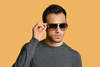 Stylish young man wearing sunglasses over colored background