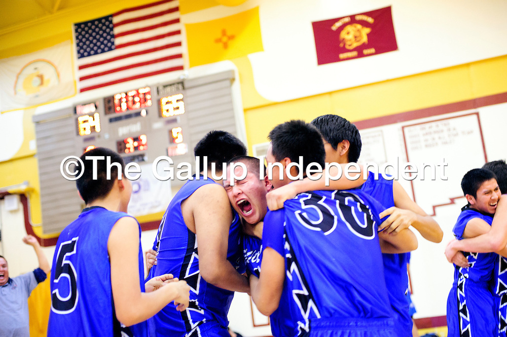 022813  Adron Gardner/Independent<br /> <br /> The Navajo Pine Warrior embrace on the basketball court after a one-point victory over the Tohatchi Cougars in the District 1-2A semifinals in Tohatchi Thursday.  The Warriors battled back from a double digit deficit in the first half brought on by strong three-point shooting from Tohatchi to beat the Cougars 65-64 at the end of regulation.