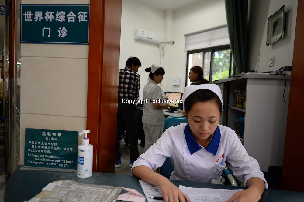 CHENGDU, CHINA - JUNE 24: (CHINA OUT) <br /> <br /> &quot;World Cup Syndrome Clinic&quot; In Chengdu Hospital Reminds Citizens To Avoid Sleep Deprivation<br /> <br />  A medical staff member sits outside the &quot;World Cup Syndrome Clinic&quot; of No. 3 People's Hospital to soccer fans on June 24, 2014 in Chengdu, Sichuan Province of China. Over a week after the 2014 World Cup began, the No. 3 Peoples Hospital in Chengdu opened a &quot;World Cup Syndrome Clinic&quot;, specifically for soccer fans that developed health issues from staying up late to watch the World Cup. A spokesperson of the hospital says that everyday since the World Cup began, there have been patients coming in for counselling or treatment on sleep deprivation caused by staying up all night to watch the World Cup. There have also been cases when fans overeat while watching the World Cup, causing burden in the gastrointestinal tract. The spokesperson says that sleep deprivation can cause mood depression and anxiety, decreased immune function, and can easily lead to neurasthenia or flu symptoms.<br /> &copy;Exclusivepix