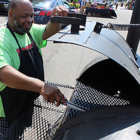 Eugene Ford of Hopewell cleans his grill between  morning and evening rushes at his booth, Ford's Roadside Bar-B-Que.