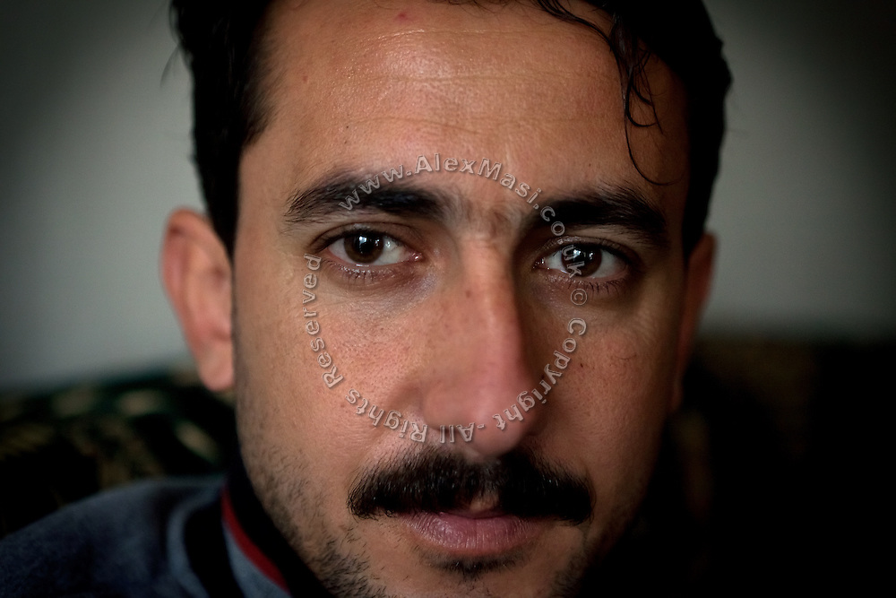 Hamed Hamid, 30, a local policeman and the son of a police Colonel who was murdered by Al-Qaida supporters for its supposed collaboration with American forces, is sitting in his home in Fallujah, Iraq. Hamed has a boy, Maath, 6, suffering from a shortage of brain cells and mental disability. The parents and their relatives have no history of birth defects.