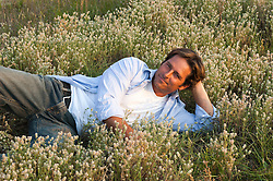 handsome man lounging in a field of wildflowers