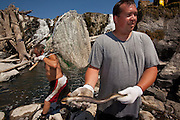Umatilla tribe member and fisheries biologist Aaron Jackson holds a pacific lamprey (Lampetra tridentata) while Umatilla tribe member Tony Montoya walks behind him with collecting nets. Water flowing over Willamette Falls (background) was restricted so tribe memebers from the Columbia River Basin could exercise their treaty rights to fish for lamprey.