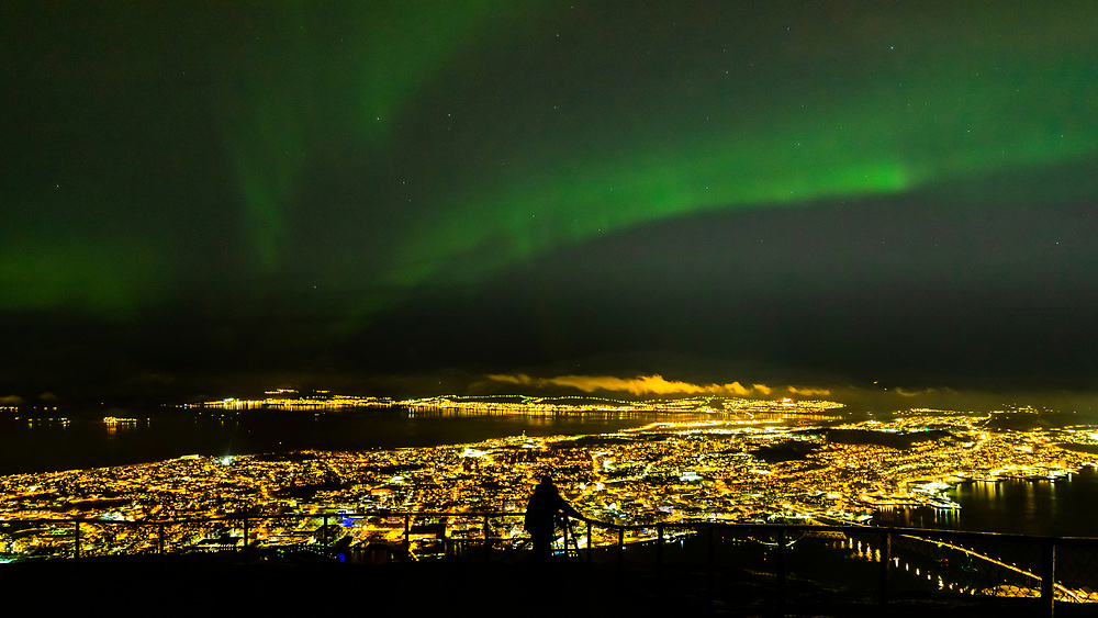 A lone person takes in the view of the Northern lights (Aurora Borealis) in the sky above the city of Tromso, Norway. Seen from the top of the Fjellheisen  aerial tramway. Tromso sits 217 miles north of the Arctic Circle and is the largest city in Northern Norway.