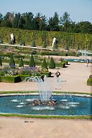 Palace of Versailles. The garden seen through old glass.
