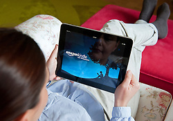 Woman using iPad tablet computer to find and read books using Amazon Kindle application