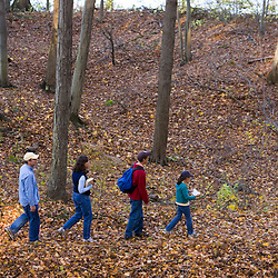 A family on a fall hike in the woods at Massachusetts Audubon Society's Arcadia Wildlife Sanctuary in Northampton, Massachusetts.  Mill River is in the background.