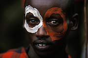 A young Hamar man with painted face who takes part in a bull jump, a ritual at which a man runs across the backs of a row of bullocks in order to become eligible for marriage, in South Omo, Ethiopia. The man is a maz, somebody who has completed the bull jump but has yet to marry, and the painted rings around his eyes show that he performed the jump eight days ago. The 40,000-strong, cattle-herding Hamar are among the largest of the 20 or so ethnic groups which inhabit the culturally diverse Omo region in south-west Ethiopia.