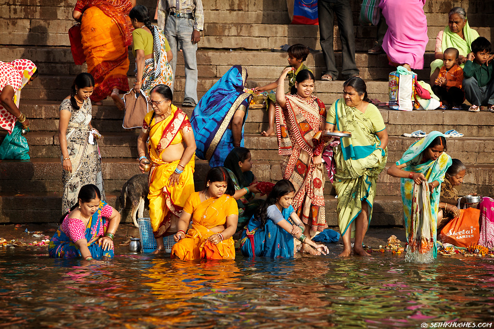 Indian women dressed in colorful saris do their morning cleansing and worshiping on the bank of the holy Ganges River in the sacred city of Varanasi, Uttar Pradesh, India. March 30, 2008