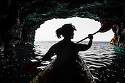 Woman kayaking in a sea cave on the Kona Coast, The Big Island, Hawaii USA