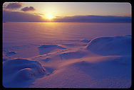 THE SUN RISES OVER FROZEN LAKE SUPERIOR COVERED WITH FRESH SNOW IN MARQUETTE MICHIGAN.