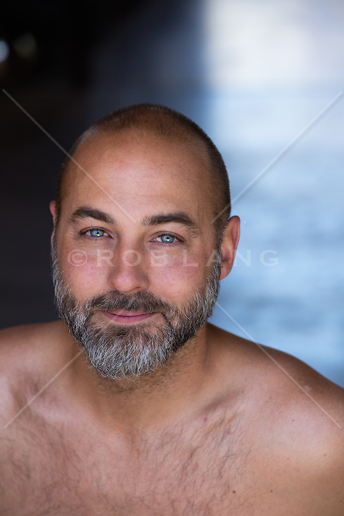 portrait of a handsome bald man with blue eyes and a gray beard