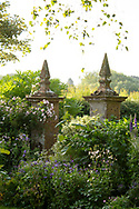Stone pillars on a gate surrounded by herbaceous borders at Lower Severalls Farmhouse,  Crewkerne, Somerset, UK